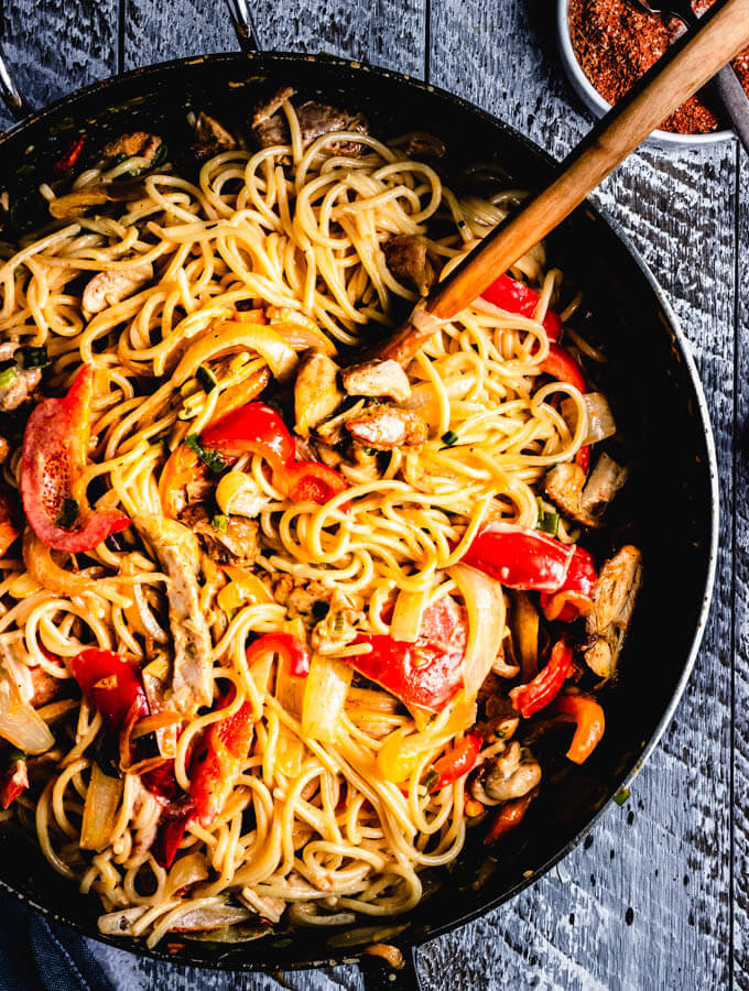 Cajun Chicken Pasta Recipe with chicken, bell peppers, onions, tomatoes, cajun seasoning, and cream.
