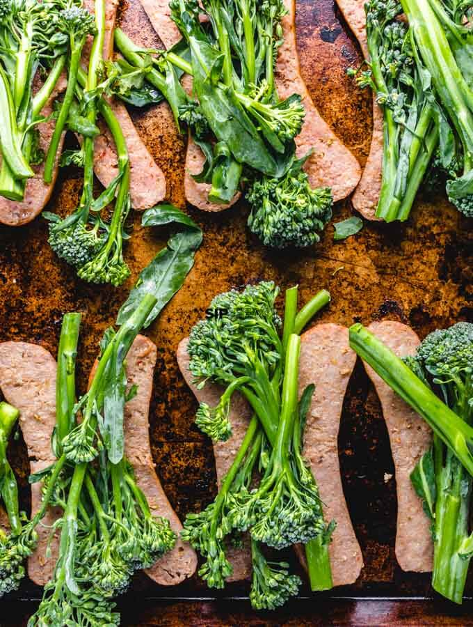 The sausage is topped with fresh broccolini.