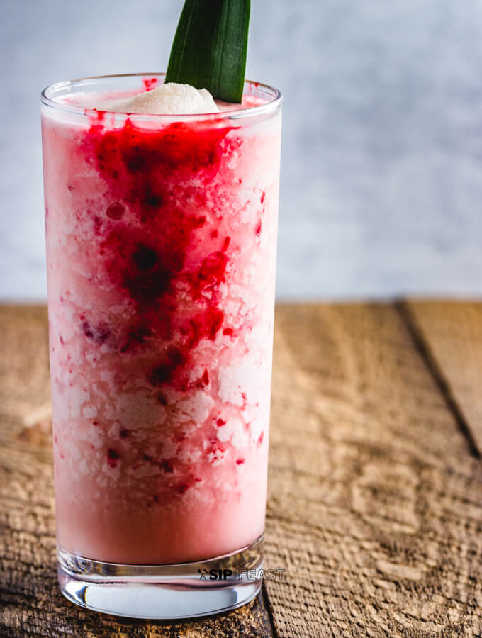 Raspberry Colada Cocktail with fresh pineapple and lime juice. A raspberry puree is added to the coconut milk and rum cocktail.