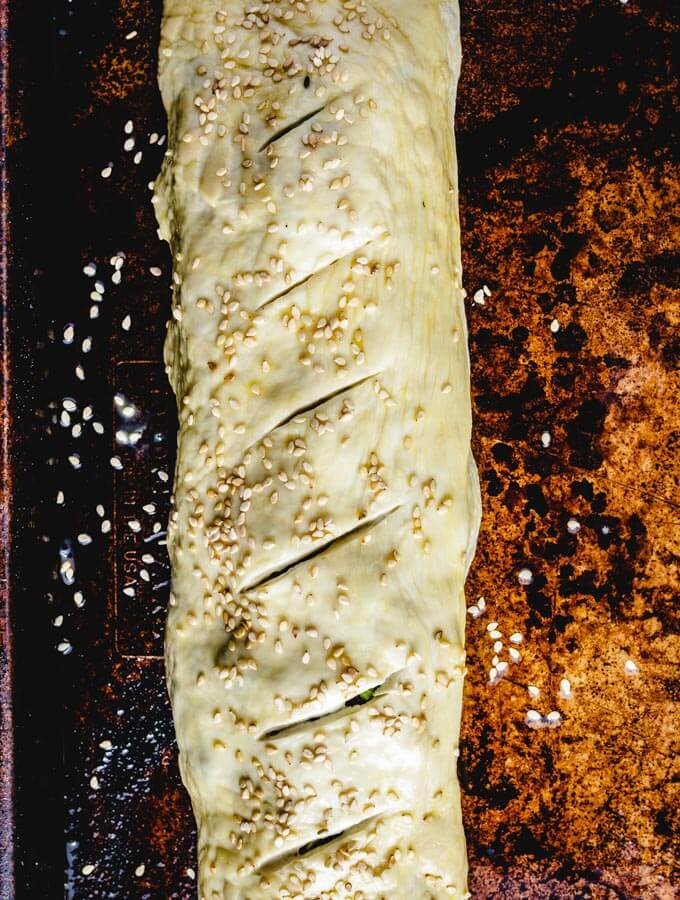 The sausage roll is formed and pinched together. Slits are made on top and an egg wash and sesame seeds are applied.