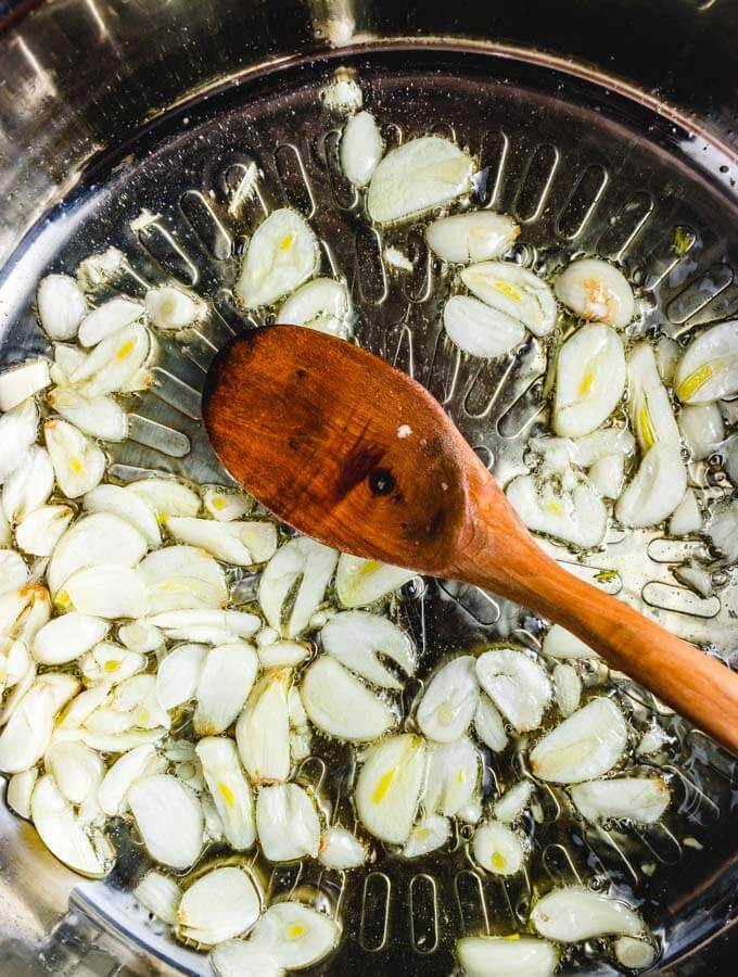 Sliced garlic being sauteed for the red sauce.
