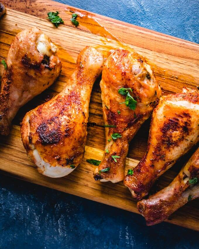 Baked chicken legs plated on cutting board.