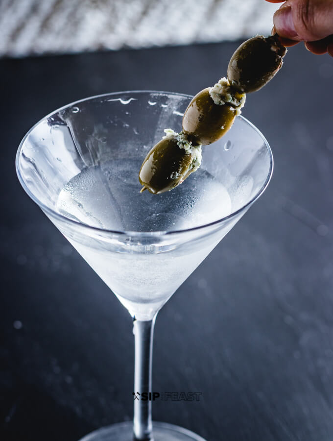 Placing 3 blue cheese olives into the martini.