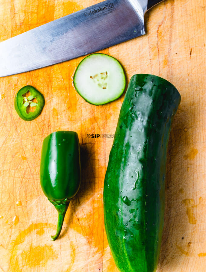 Slices of cucumber and jalapeno and a knife.