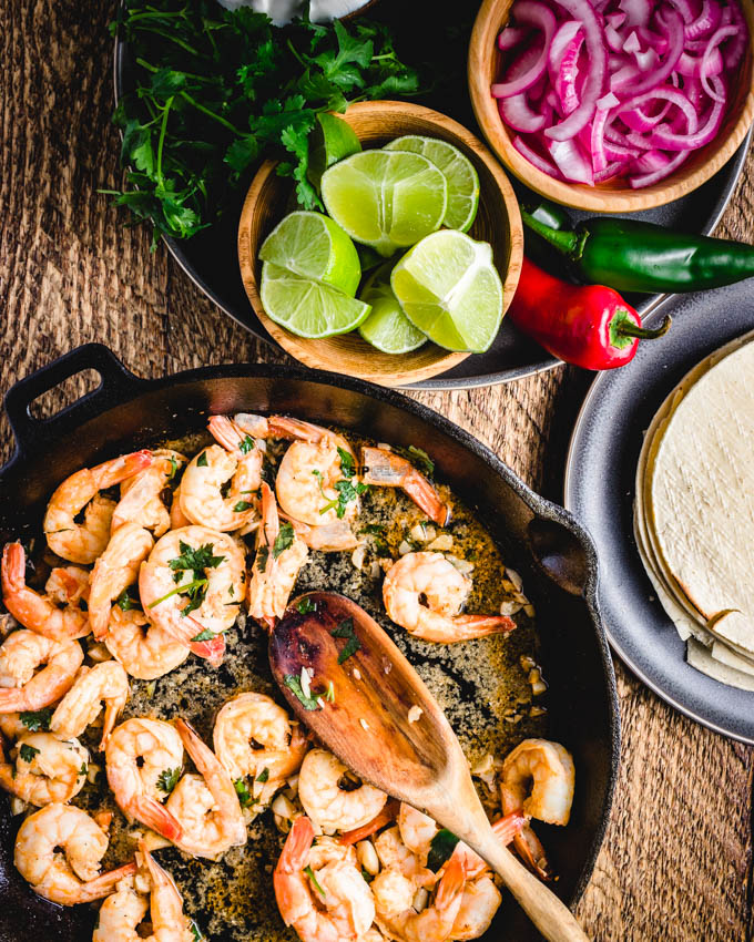 Shrimp taco recipe with limes, marinated red onions, tortillas, and cilantro.