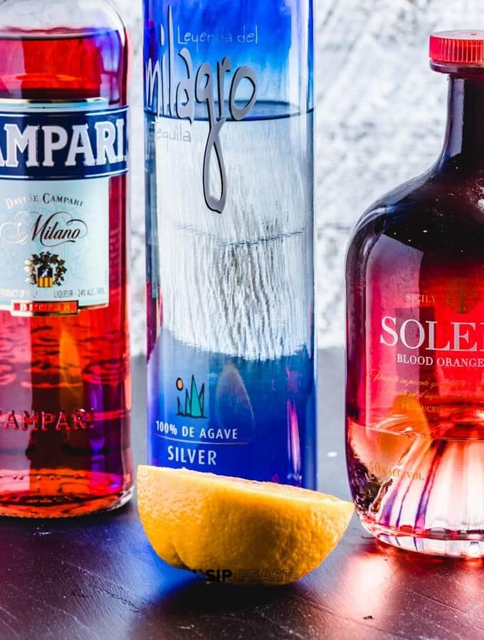 A bottle of Campari, bottle of tequila, bottle of Solerno blood orange liquor and half an orange.