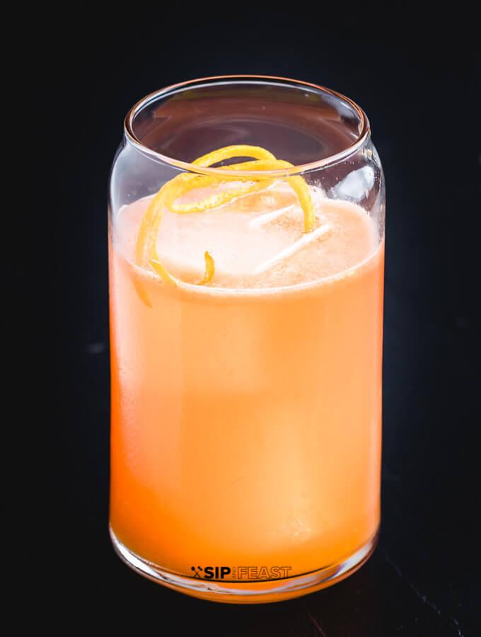 A glass with the Italian Margarita, Ice and Orange peel.