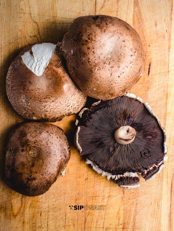 Portobello mushrooms on cutting board.