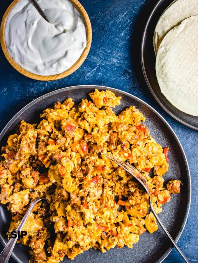 Plated Chorizo and eggs with sour cream and tortillas.