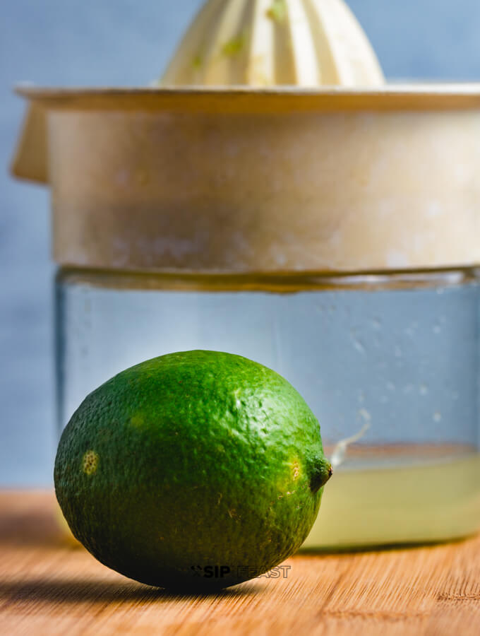 A citrus juicer with lime juice and a full lime.