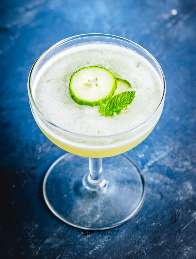 A coupe glass with the cucumber martini with melon garnished with cucumber slices and a mint leaf.