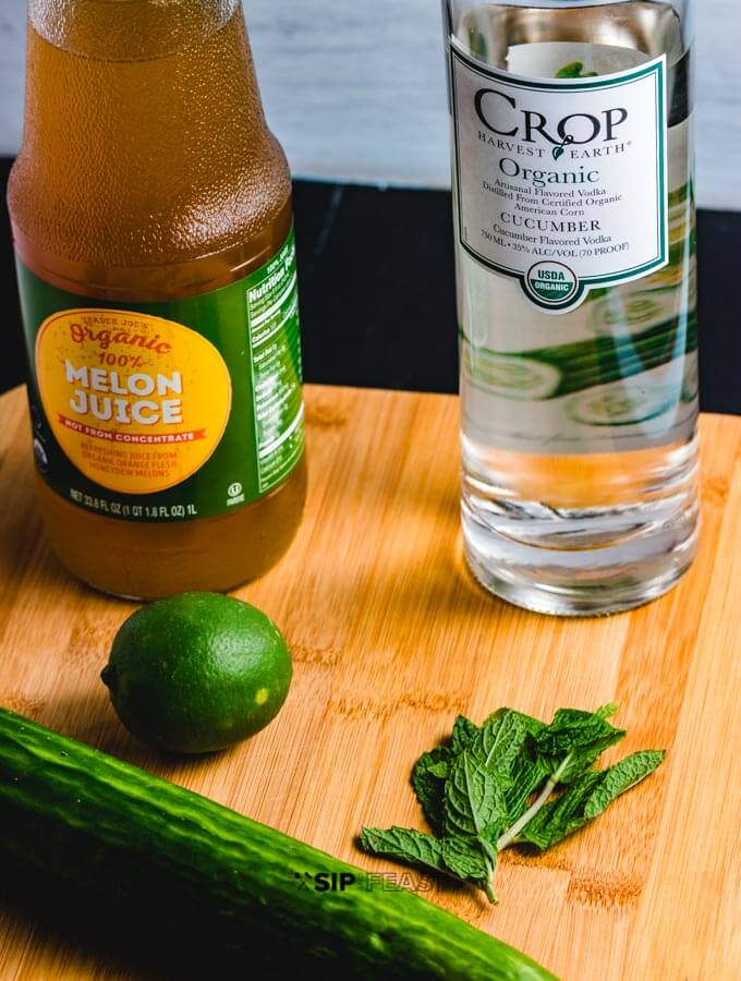 Bottle of Crop Organic Cucumber Vodka, bottle of melon juice, 1 lime, sprig of mint and cucumber.