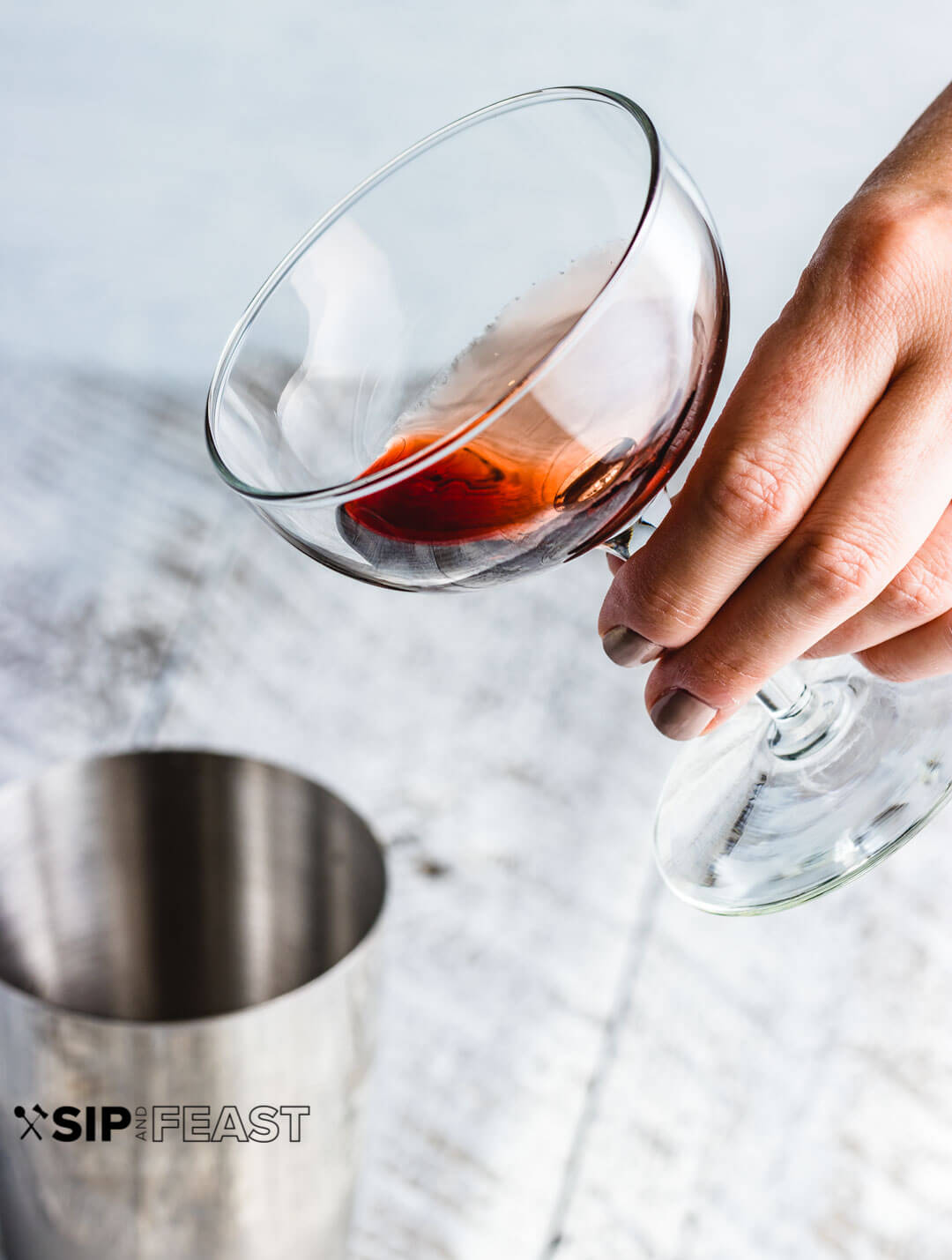 Hand holding a coupe glass with a coating of cherry syrup.