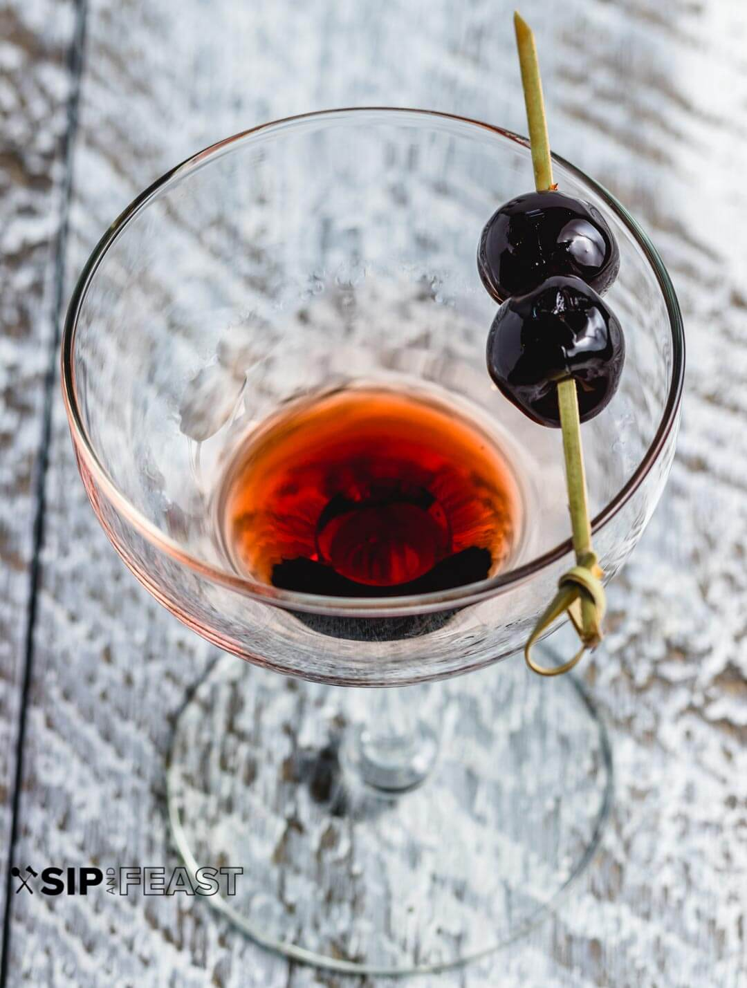 A glass with cherry syrup and two cherries on a toothpick.
