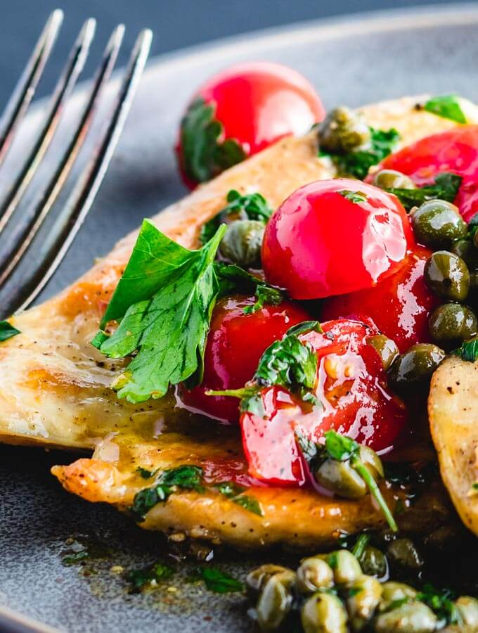 Italian chicken with capers and cherry tomato sauce closeup.
