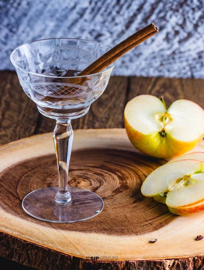 Cocktail glass with cinnamon stick, and sliced apples on a cutting board.