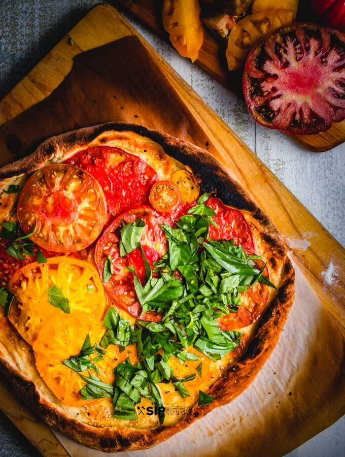 Cheeseless Pizza with heirloom tomatoes and basil featured image.