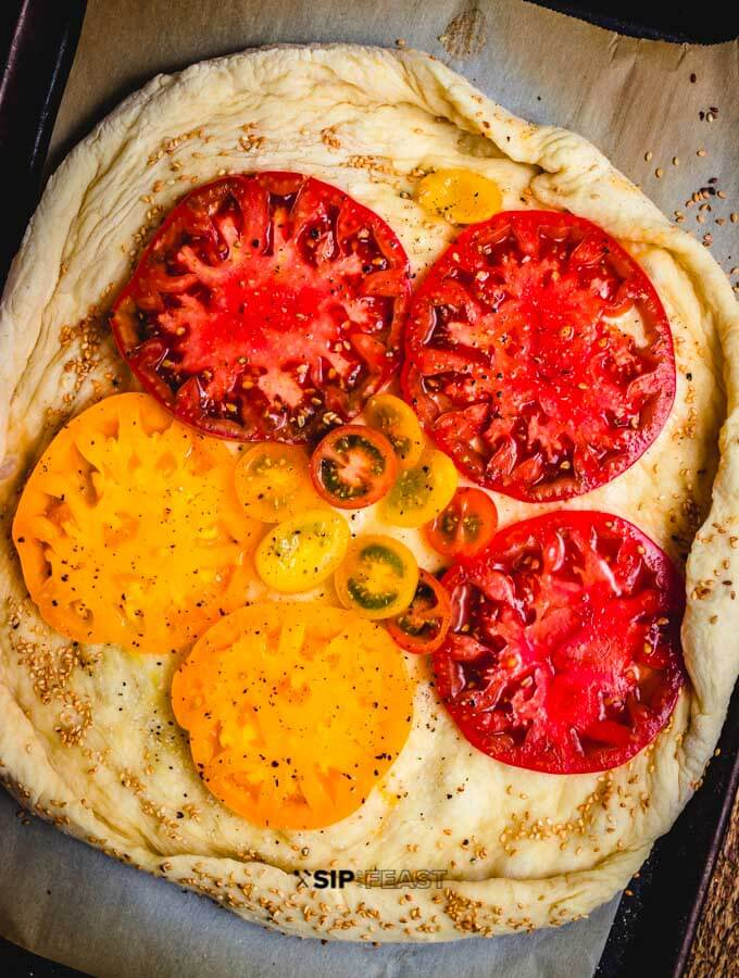Heirloom tomatoes placed on top of the pizza dough.