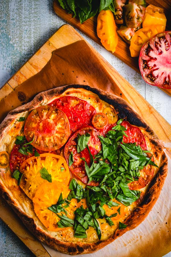 Cheeseless pizza with heirloom tomatoes and fresh basil Pinterest image.