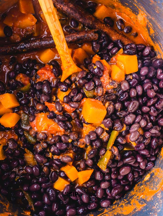 Adding the black beans to chili pot.