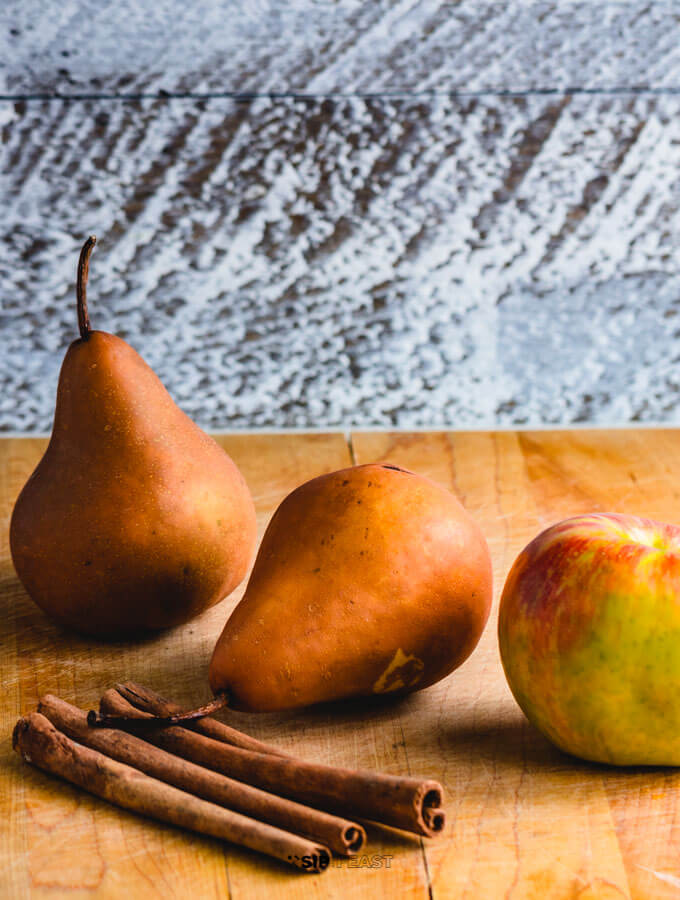 Pears, apple and cinnamon sticks on a cutting board.