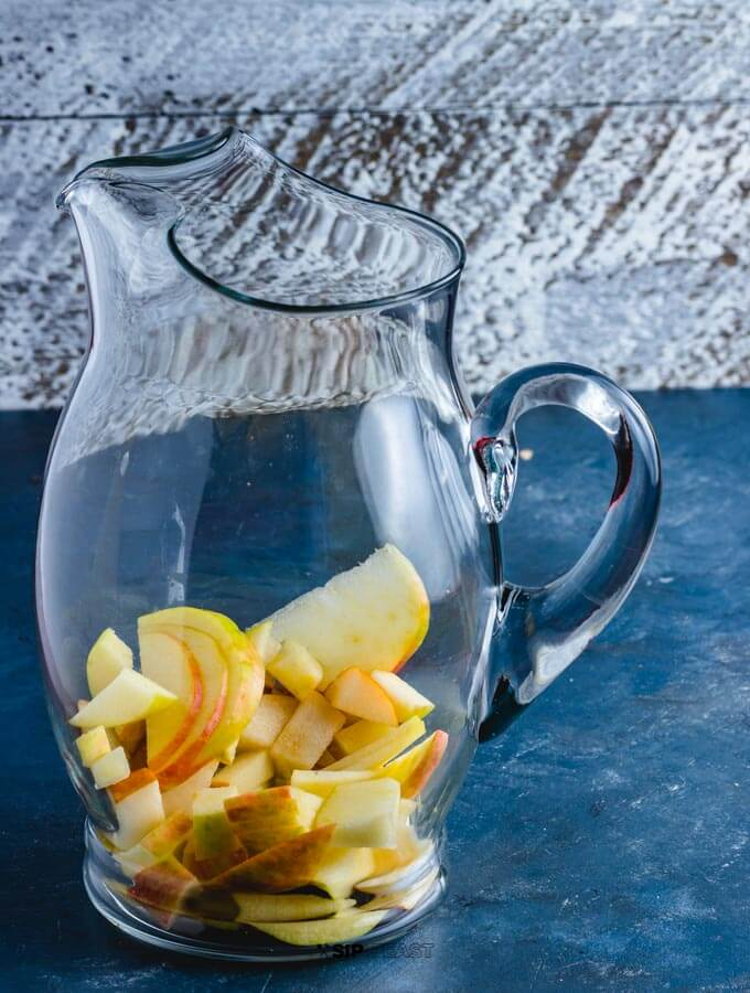 The apples and pears and liquor in the sangria pitcher.