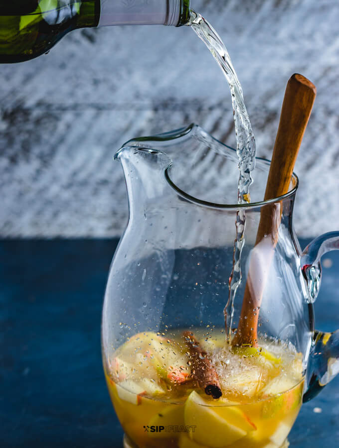 White wine being poured into a sangria pitcher with apples and pears.