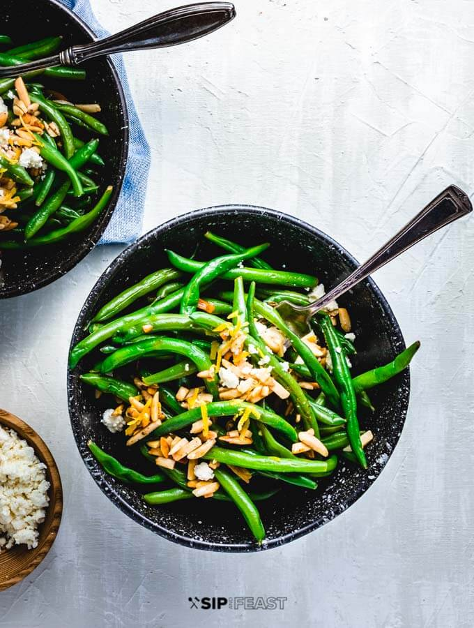 Green beans almondine with feta in 2 bowls.