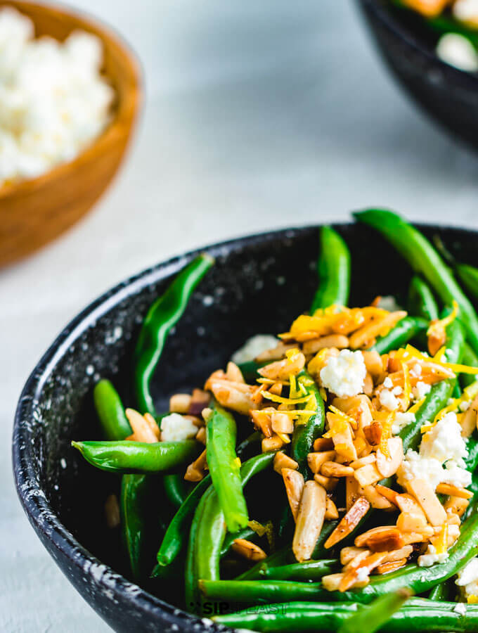 Green beans almondine with feta in serving bowl.