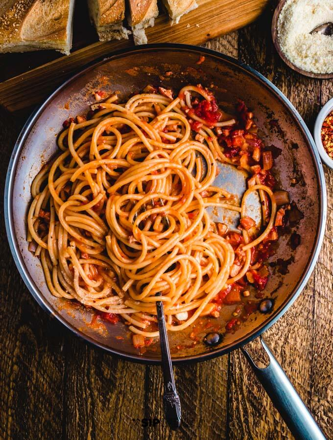 Spaghetti amatriciana in pan on table with cheese, bread, and hot pepper flakes.