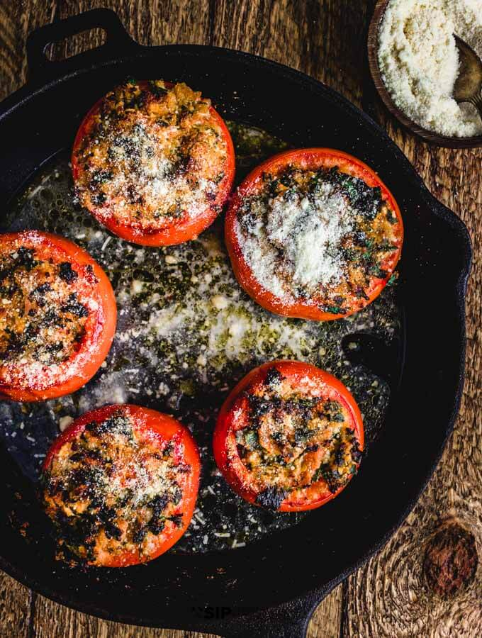 Easy stuffed tomatoes with ricotta salata and parsley overhead shot in cast iron pan.