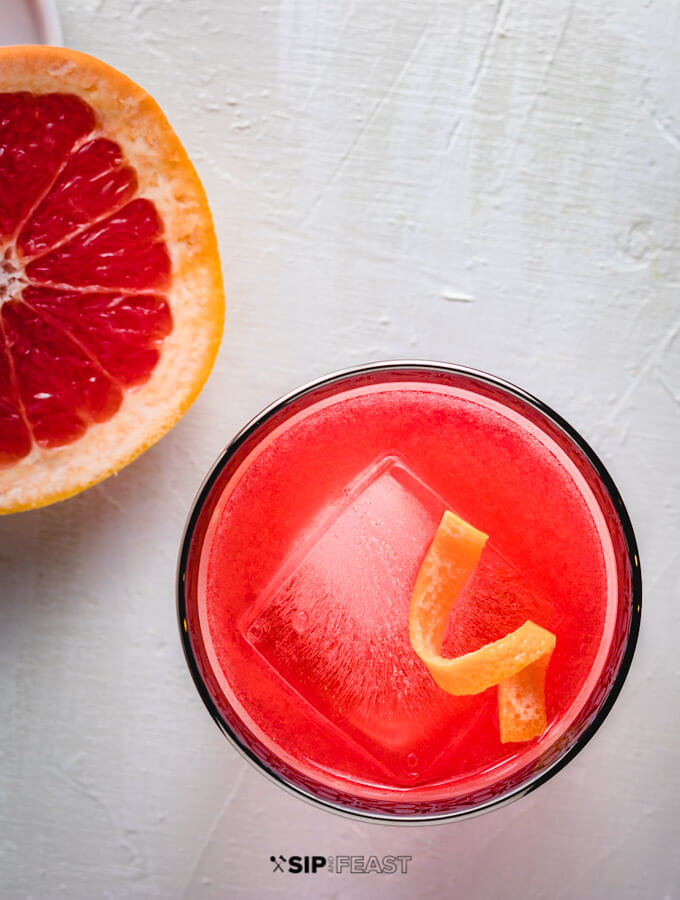 A glass of the grapefruit gin negroni with a twist of grapefruit peel