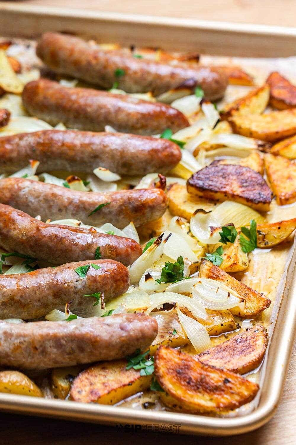Easy Italian sheet pan dinner recipe.  Italian pinwheel sausage is layered on top of thin sliced potatoes with cherry peppers, vinegar, and extra virgin olive oil.  Super simple weeknight dinner idea. #Italianrecipe #sheetpandinner #sausagerecipe #potatorecipe #easyrecipe #onepanrecipe