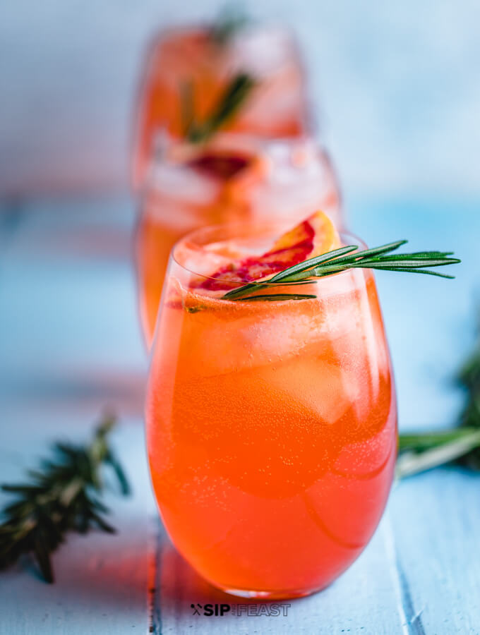 Aperol Spritz cocktail in three wine glasses with orange and rosemary garnish.