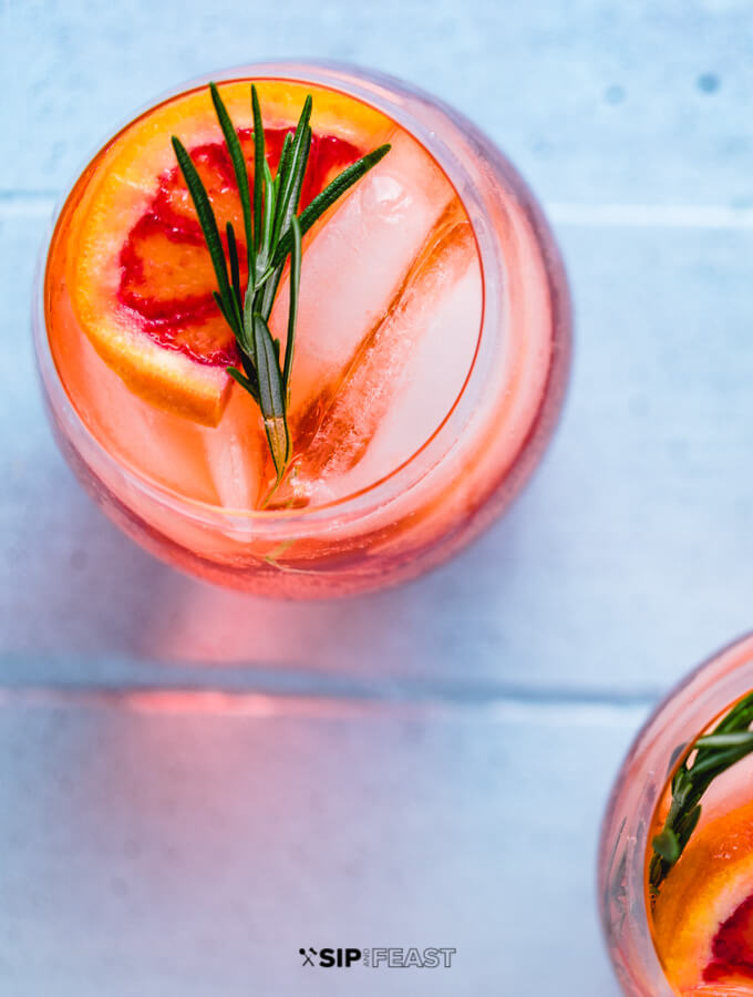 Aperol Spritz in wine glass with ice, rosemary and orange slice.