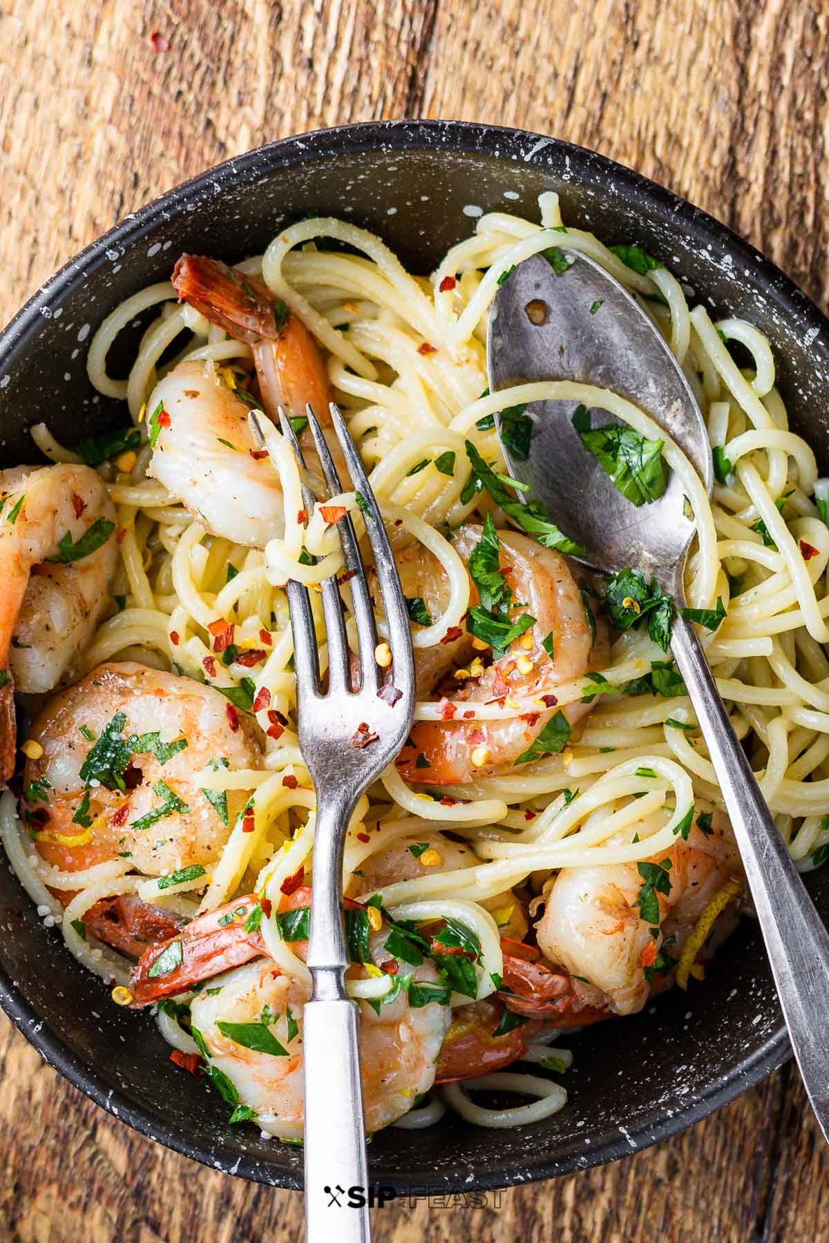 Lemon Garlic Shrimp Pasta - Quick and easy weeknight meal that will impress everyone.  This delicious pasta recipe can be made in 30 minutes! #sipandfeast #shrimp #shrimppasta #spaghetti #seafood #easydinnerrecipe #pastarecipe #italianrecipe #noodles
