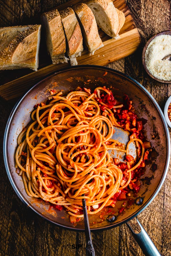 Spaghetti Amatriciana - A delicious Italian comfort food pasta dish. Made with pancetta over guanciale to make an easy recipe with accessible ingredients.  The whole recipe can be on your table in under 30 minutes. #pastarecipe #pancetta #italianrecipe #pasta #tomatosauce #amatriciana