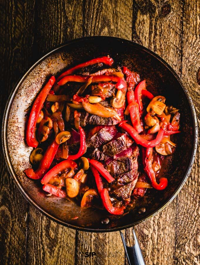 beef steak with red bell peppers in a dark skillet