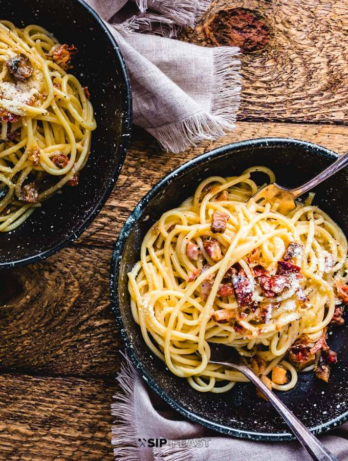 Spaghetti carbonara plated in two bowls.