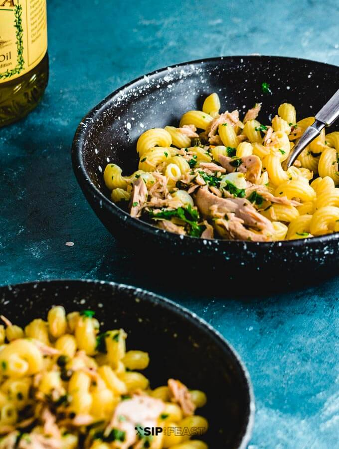 Tuna pasta in two plates with olive oil on side.
