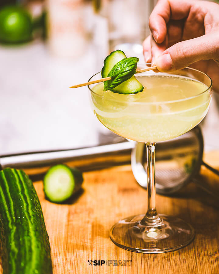 Placing the cucumber and basil garnish in the cocktail.