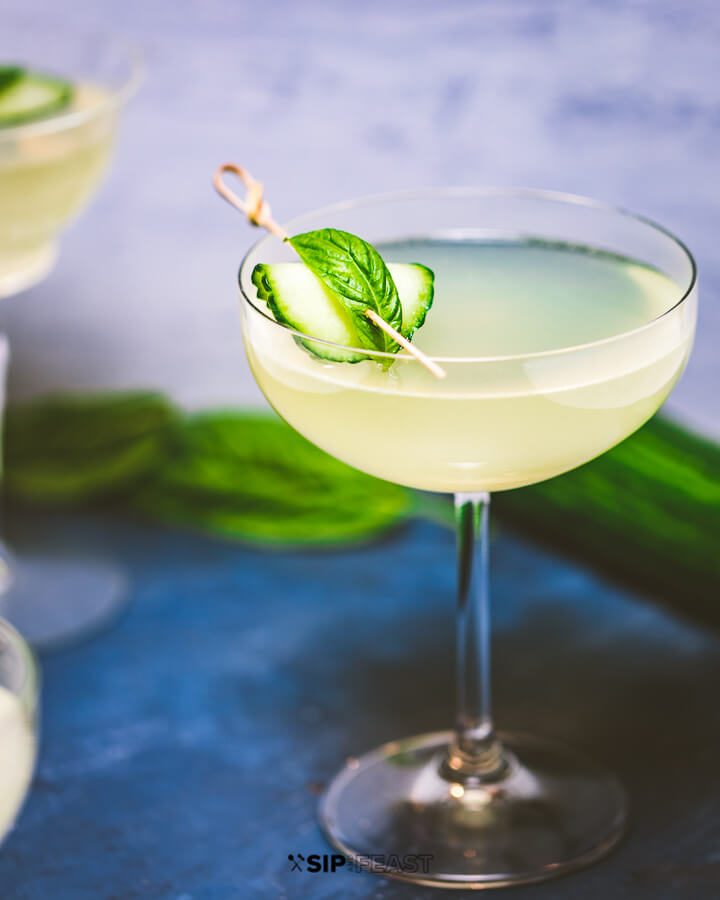 Limonata basil cocktail in a coupe glass with cucumber and basil garnish.