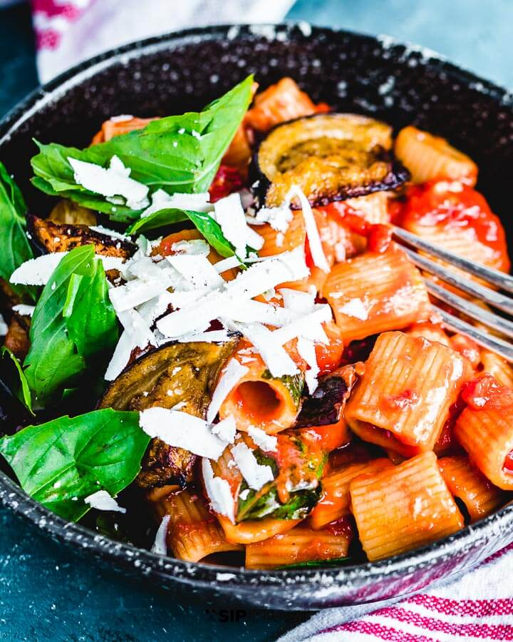 Rigatoni alla norma plated in bowl with extra basil and ricotta salata.