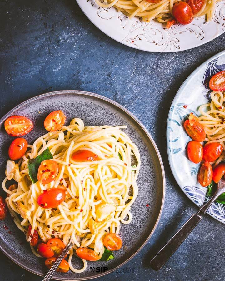 Three plates of spaghetti and tomatoes on blue background.