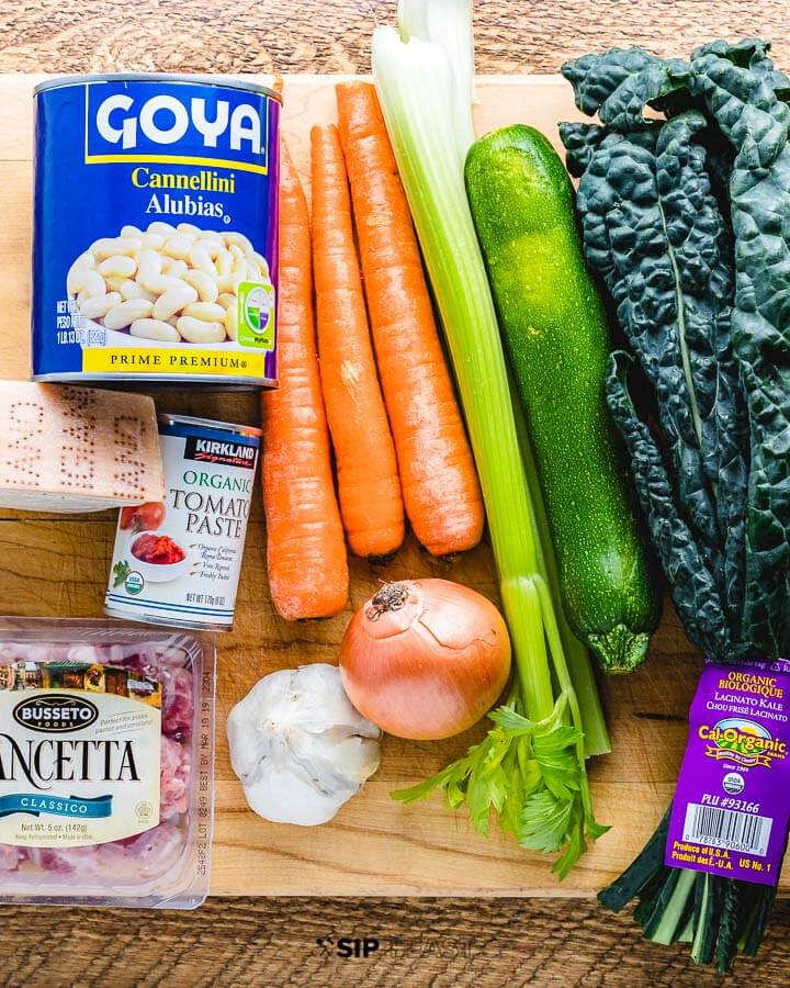 Tuscan soup ingredients shown: beans, pancetta, carrots, zucchini, kale, cheese, tomato paste, garlic and onion.
