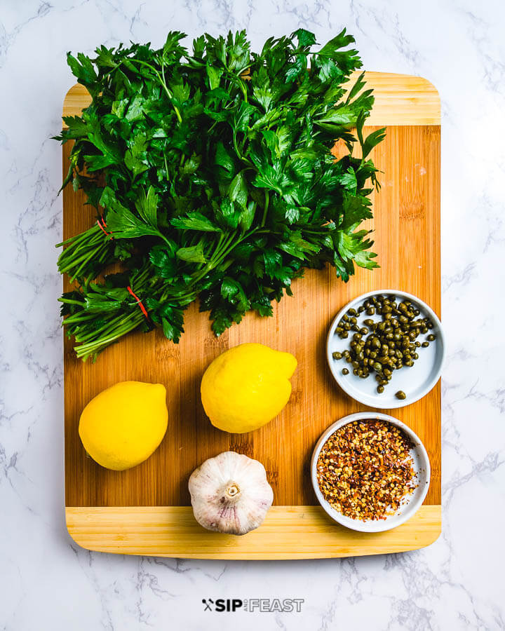 Italian salsa verde ingredients shown on cutting board: parsley, lemons, capers, garlic and chili flakes.