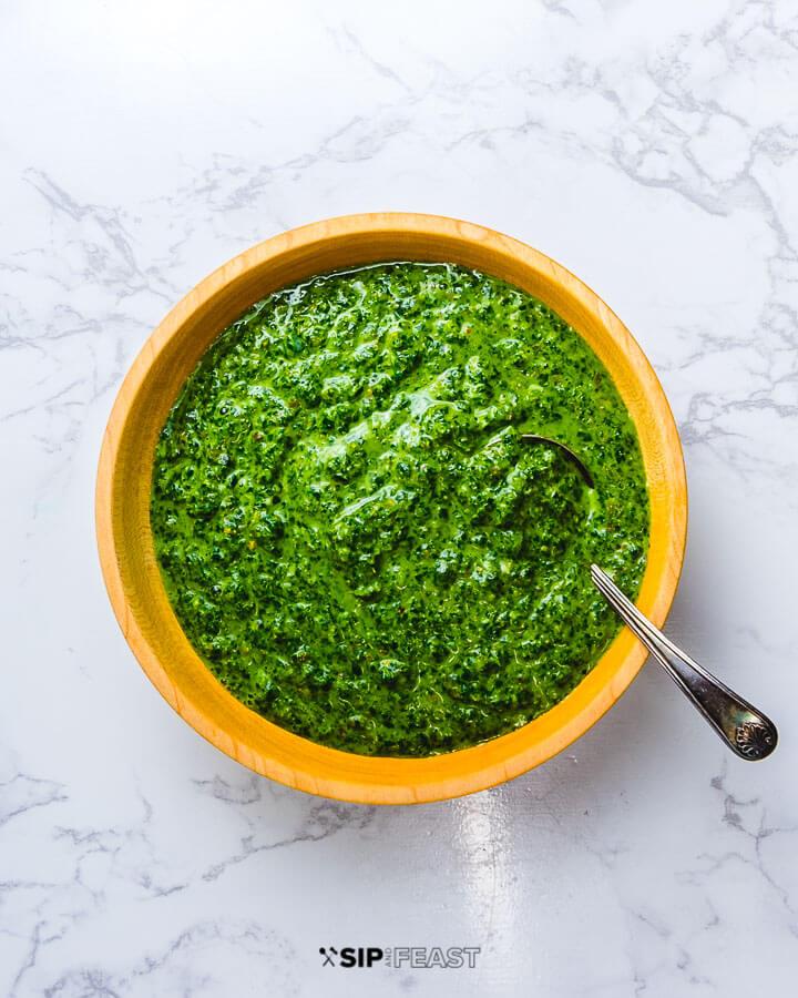 Italian green sauce in wooden bowl on white granite.