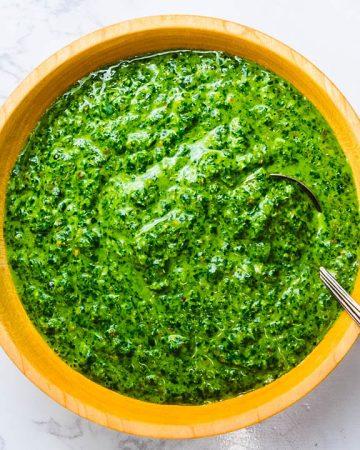Italian salsa verde in wooden bowl on white granite.