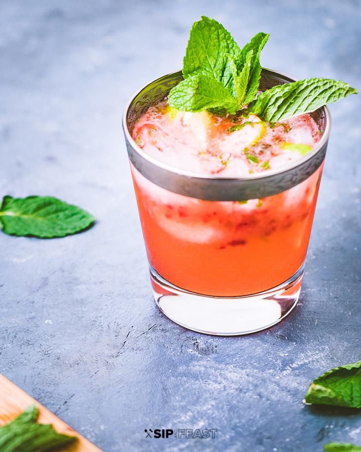 Strawberry mojito in a glass with mint leaves on blue table.