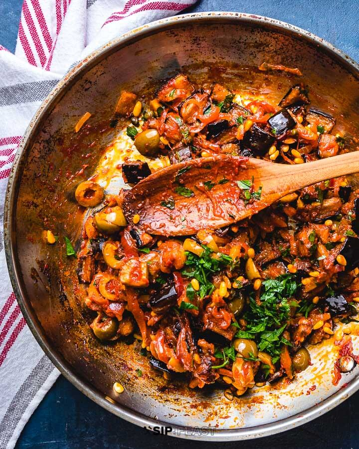 Pan of caponata with large wooden spoon.